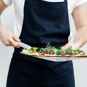 Vegetarian flam-kuche or skinny pizza topped with fresh herbs and served on a tray