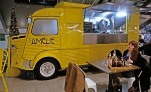 Debbie Helen at Amelie Restaurant in front of the yellow van