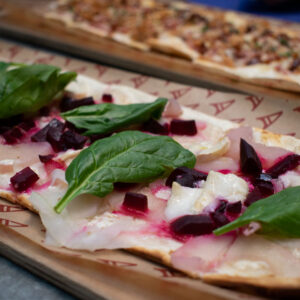 Beetroot and pear flammekueche with spinach leaves on top