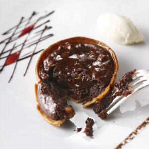 Dark chocolate and hazelnut tartlet with whipped cream on a plate with a fork