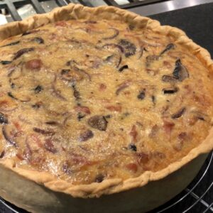 French Quiche with mushrooms and onions cooling down on a rack